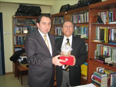 Üniversitemiz Rektörü Prof. Dr. Reha Metin ALKAN, Prof. Dr. Mehmet KESİM'e plaket takdim ederken